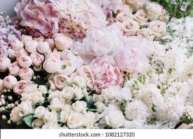 Beautiful flower bed of fresh peonies, roses, hyacinths, hydrangeas, ranunculus in tender pink colors at the florist shop, top view