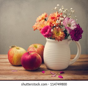 Beautiful flower bouquet and fresh apples on wooden tabletop