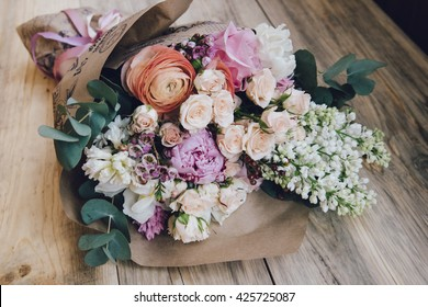 Beautiful flower bouquet of fresh white lilac, roses, ranunculus, peony, hyacinth, eucalyptus on the wooden rustic table