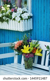 Beautiful flower bouquet with lily and other flowers on a garden bench