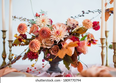Beautiful flower composition with autumn orange and red flowers and berries. Autumn bouquet in vintage vase on a wooden table with pink tissue and candles