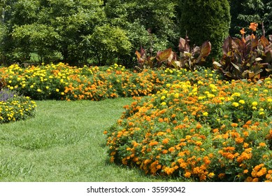 Beautiful flower gardens in a park with curving lawn pathways, horizontal with copy space