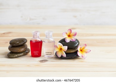 Beautiful flower on rock  with soap, shampoo on wood background.