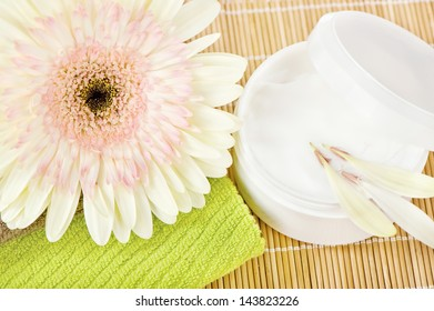 Beautiful flower on top of green towel with skin care product