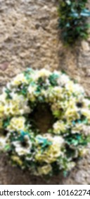Beautiful flower wreath on the wall of an old house. Blurred view