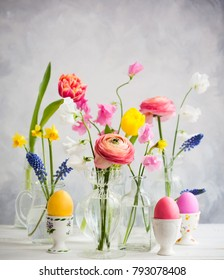 Beautiful flowers bouquets in glass vases on festive Easter table. Colored Easter eggs in egg cups.