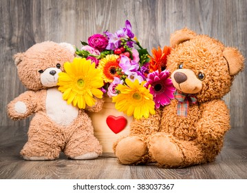 Beautiful flowers in the box and teddy bears on wooden background