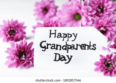 Beautiful flowers and card with phrase Happy Grandparents Day on white table, closeup