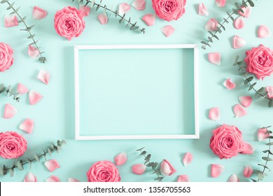 Beautiful flowers composition. Blank frame for text, pink rose flowers,  eucalyptus leaves on pastel mint background. Valentines Day, Easter, Birthday, Mother's day. Flat lay, top view, copy space