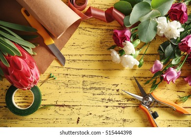 Beautiful flowers and florist equipment on yellow wooden background