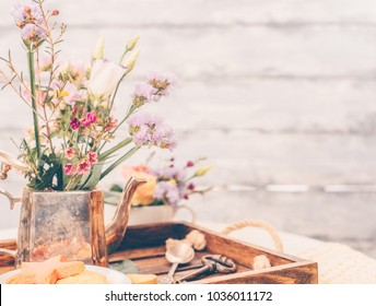 Beautiful flowers in old vintage tea pot on beautiful wooden tray, spring mood still life photo for holiday design