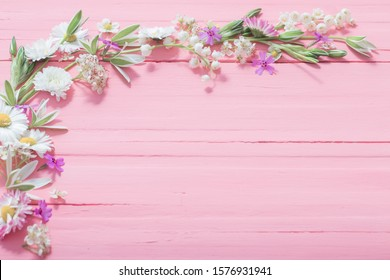beautiful flowers on pink wooden background
