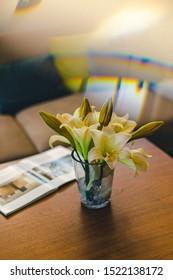 Beautiful flowers on a table near a magazine