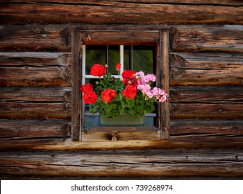 Beautiful flowers on a window of old traditional farmhouse in austria