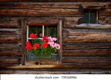 Beautiful flowers on window of old traditional farmhouse in austria