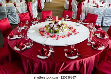 Beautiful flowers are placed on the table covered with red tablecloth, wedding hall
