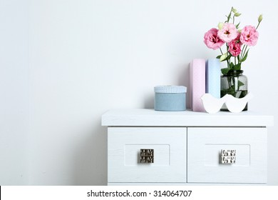 Beautiful flowers in vase with books on wall background