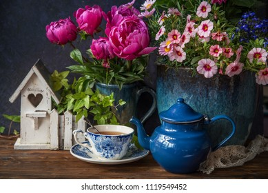 Beautiful flowers in vase and cup of tea at wooden table, summer decor