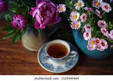 Beautiful flowers in vase and cup of tea at wooden table. Selective focus