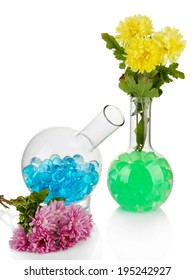 Beautiful flowers in vase with hydrogel isolated on white