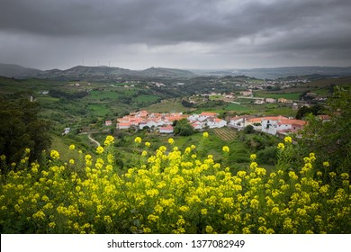 Beautiful and flowery countryside with a small village in a distance on a cloudy Spring day