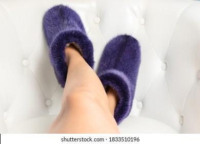 Beautiful fluffy fur footwear on women legs. - Shutterstock ID 1833510196