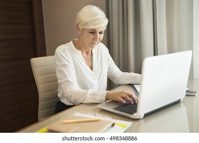 Beautiful focused businesswoman sitting at a desk working on a laptop