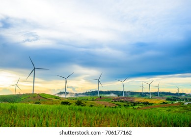 Beautiful fog mountain landscape and wind generators turbines at sunset, Khao Kho mountain, Thailand. Renewable energy concept.