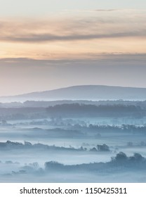 Beautiful foggy English countryside landscape at sunrise in Winter with layers rolling through the fields