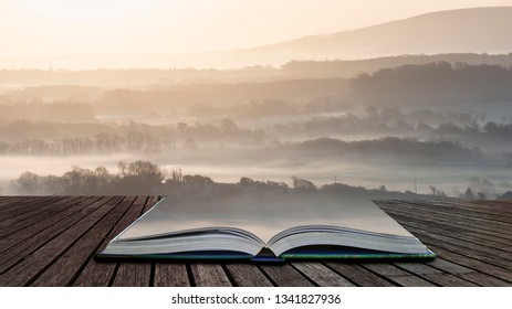 Beautiful foggy English countryside landscape at sunrise in Winter with layers rolling through the fields coming out of pages in magical story book