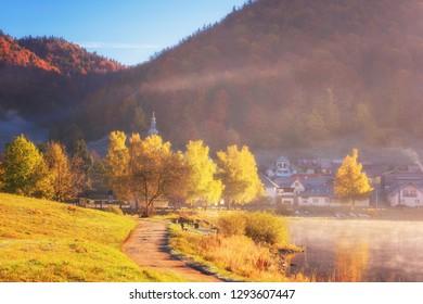 Beautiful foggy and frosty autumn morning landscape with lake, small village and mountains, outdoor travel background, Dedinky, National park Slovak paradise (Narodny park Slovensky Raj), Slovakia - Shutterstock ID 1293607447