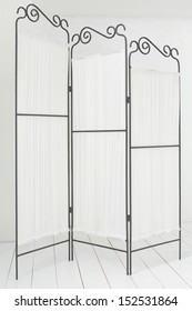 Beautiful folding screen made �¢??�¢??of metal and fabric in a light room