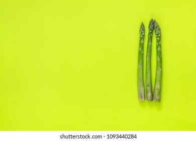 Beautiful food art background. Asparagus sprouts on bright green surface.