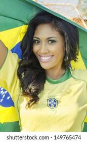 Beautiful football fan soccer in Brazilian color holding Brazil flag,