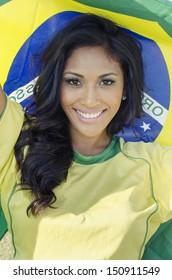 Beautiful football fan soccer in Brazilian color holding Brazil flag