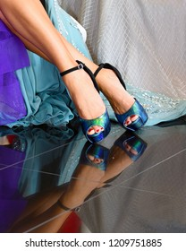 Beautiful formal dress shoes on woman's feet. High heels with iridescent color show reflection on ballroom floor