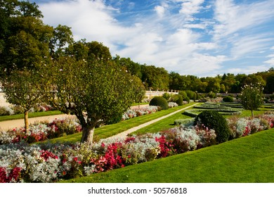 A beautiful formal garden in France, with flowers, plants and sculpted hedges, on a sunny day.