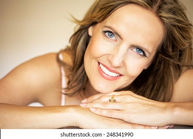 Beautiful forty year old woman posing in warm-colored environment.