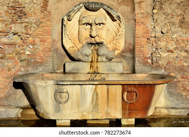 Beautiful fountain in orange gardens in Rome, Italy. Is this wonderful fountain of a giant, grotesque mask, which spits water into a giant, ancient Roman basin