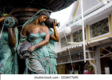 The beautiful fountain statue of a girl is pouring water.