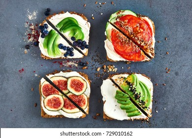 Beautiful four vegetables sandwiches with bread, avocado, tomato, fig, blueberry, nigella and cottage cheese on a grey surface top view