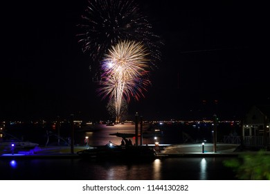 Beautiful Fourth of July fireworks glowing over Lake Coeur d'Alene in Idaho with several boats crowding the water and the dock.
