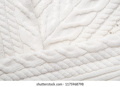 A beautiful fragment of a knitted texture of white color as an interesting background
