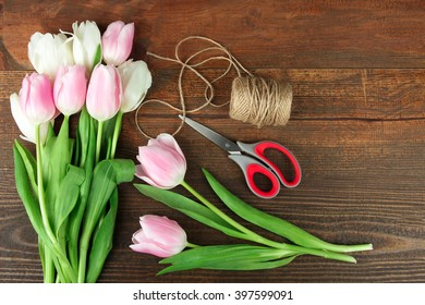beautiful and fragrant blooming pink and white tulips with a skein of thread and a scissors lying on a brown wooden background