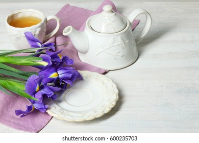 Beautiful fragrant daffodils, cup with tea and teapot on a wooden background