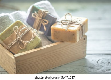 beautiful, fragrant handmade soap in wooden box standing on a wooden background