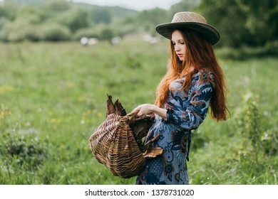 beautiful freckled young woman wearing straw hat at sunset time on the meadow