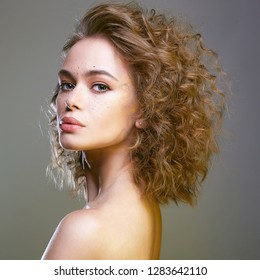 Beautiful freckles woman. amazing curly hairstyle girl. beauty fashion portrait. frizzle hair