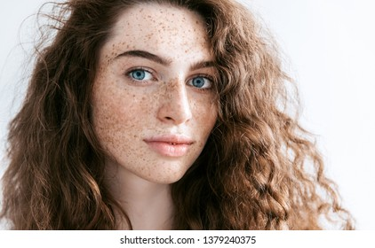 Beautiful Freckles young woman close up portrait. Attractive model with beautiful blue eyes and ginger curly hair