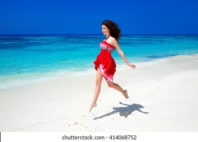 Beautiful free girl running on exotic beach with white sand and blue water. Happiness bliss freedom beach concept. Good life. Enjoyment. Summer Vacation. Nature background.